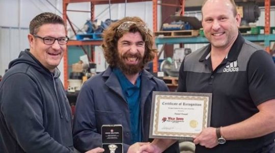 man receives work recognition award with two colleagues