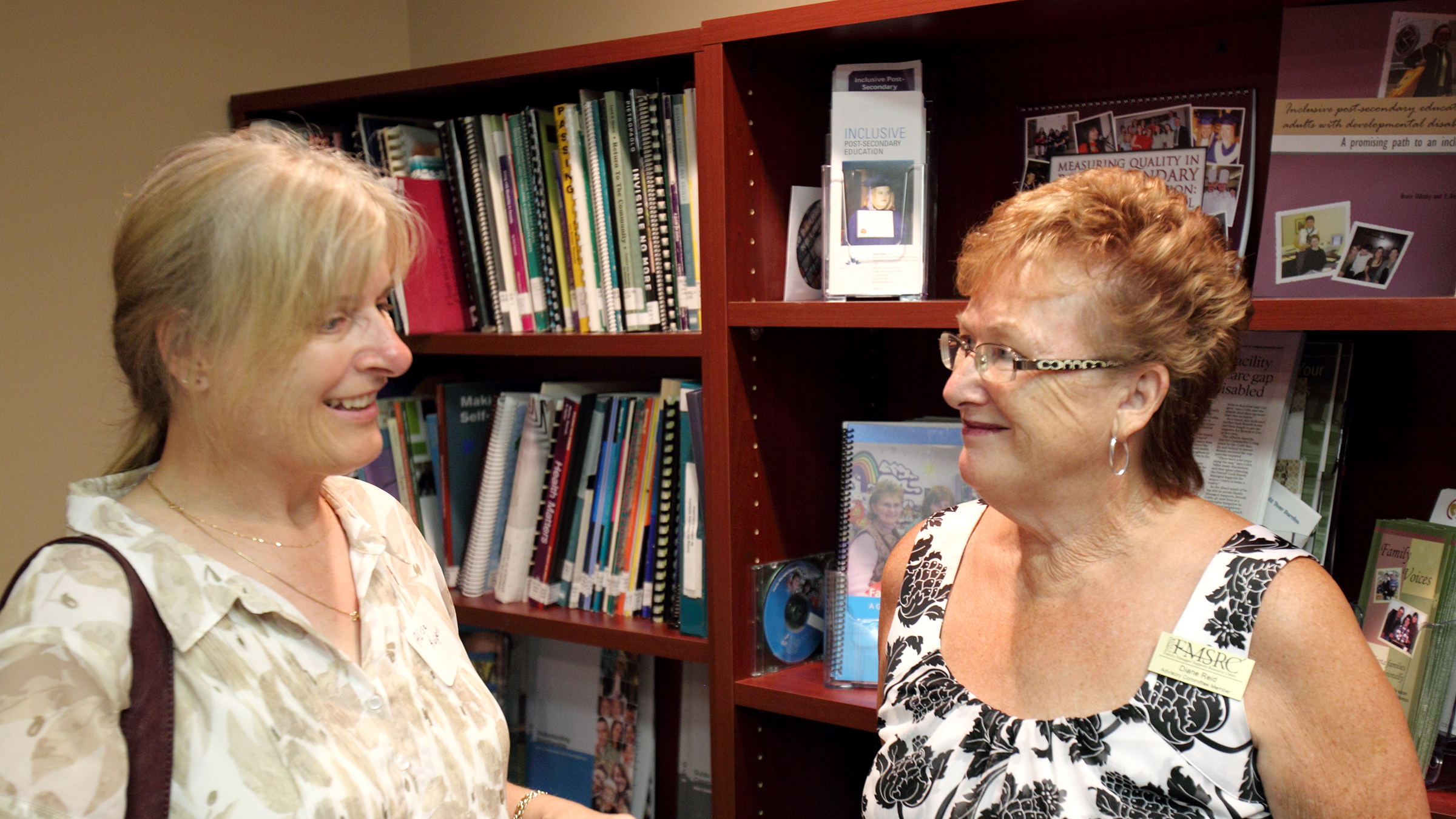 Two women smile while talking in front of full bookshelves