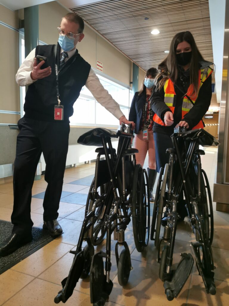 Kyle and a colleague fold up a wheelchair for a flight passenger at EIA Edmonton airport
