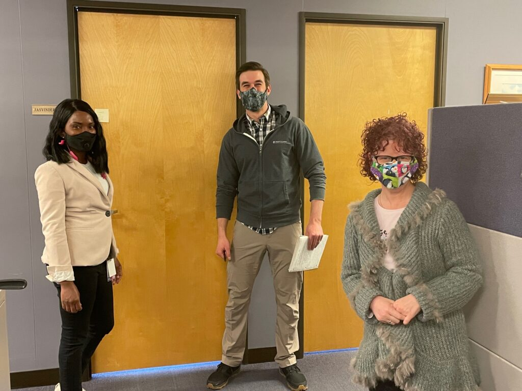 Jodi Reid stands in a socially distant manner with two other coworkers in an office, all three are wearing masks.