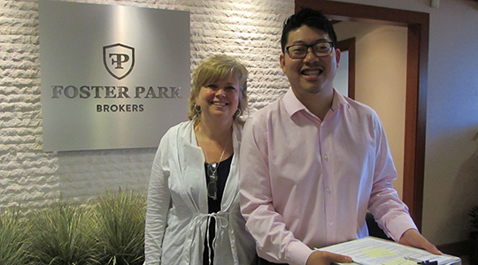 Peter Lee stands in the front lobby of Foster Park Brokers with a colleague