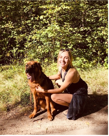 Madalyn poses in front of a forest with a dog. She is crouched down with her arms around the dog.