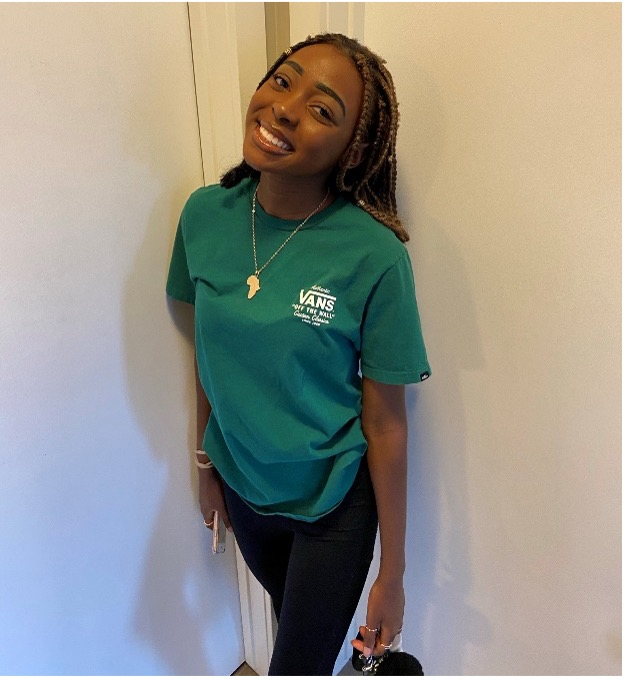 Takana poses agains a white wall, wearing black pants and a green shirt that says 'vans'. She is smiling.